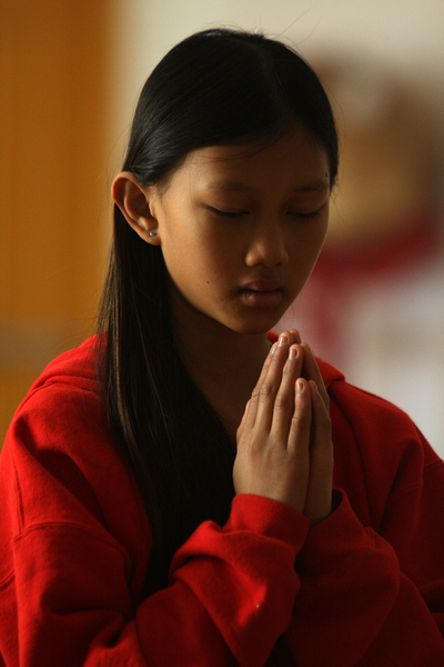 "11-year-old Emily Morgan Tracey at prayer during services. About her experiences as a Vietnamese American, she says, ""It can be hard to be Asian and American because sometimes people tease you. But believe in who you are and dont let anyone or anything stop you."""