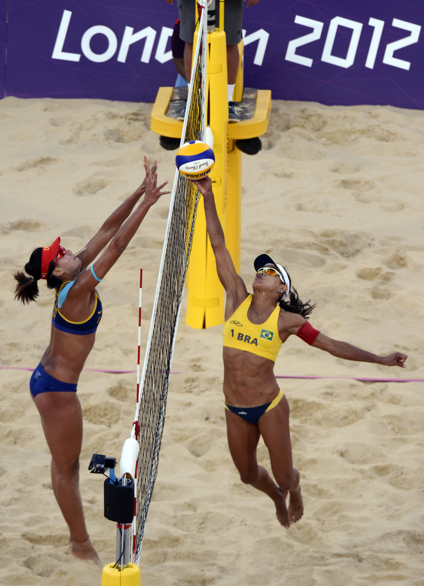 Brazil's Juliana Silva taps the ball over the net as China's Chen Xue tries to block.
