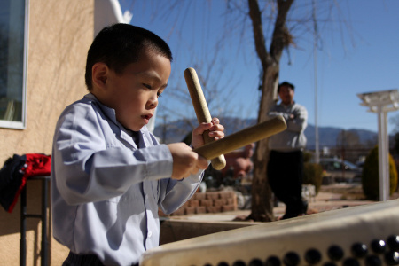 A young boy practices his drumming following youth services at the Van Hanh Buddhist Center in Albuquerque.