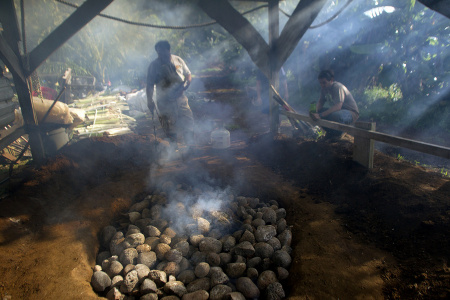 A fire tender finishes lighting an imu, a traditional Hawaiian oven of wood and stones in an earthen pit that takes community members all day to prepare. When ready, food is placed inside the imu and cooked overnight. In Kokua Kalihi Valleys Ehuola Program, children and their families participate in the preparation of the imu to better understand the cultural relationship between health, food, and the land, and to reconnect to important cultural practices.