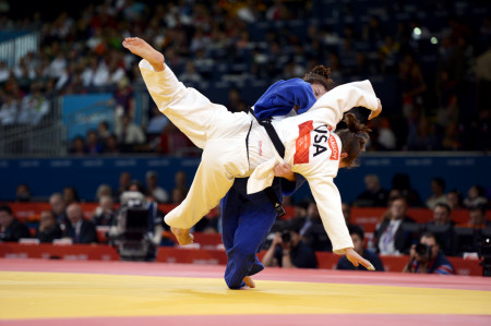 Corina Caprioriu of Romania, the eventual gold medalist, wearing blue, takes down Marti Malloy of the United States during the women's 57kg Judo competition.   Malloy won the bronze medal which she shared with Automne Pavia of France.